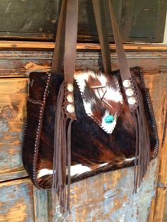 Custom Big  Bonnie with Lydia Side Pockets  lined in chocolate brown suede. This customer included her brand, buffalo nickel and Indian head conchos on the suede fringed straps and a turquoise stone. Order your custom cowhide bag at gowestdesigns.us. Happy Trails!