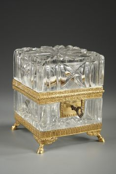 A small cut-crystal square casket with its key and gilt bronze mounts, finely chiselled with small flowers and foliages. The body is decorated with an alternation of straight coast...
