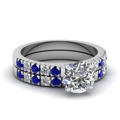 This magnificent wedding ring set features an #engagementring with a subtle prong set center stone, which is further enhanced by a series shimmering channel set princess cut #diamonds and gemstones excellently spread inline on either sides that covers the entire top portion of the #ring. http://jangmijewelry.com/