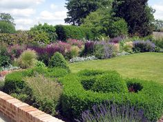 Walled Garden with boxwood, grasses, and pink and purple flowers - Amanda Patton Garden Design & Planting