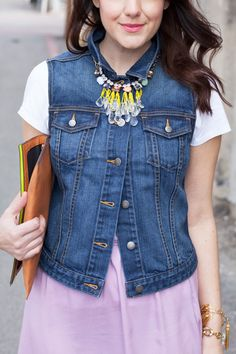 Denim vest/jacket buttoned to the top with a statement necklace over