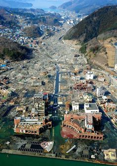 AT THE TIME OF THE DISASTER: Onagawa, Miyagi Prefecture, pictured on March 13, 2011. The tsunami destroyed the town, leveling the houses in its path and wrecking the sturdy passenger ship terminal in the foreground. (The Asahi Shimbun)