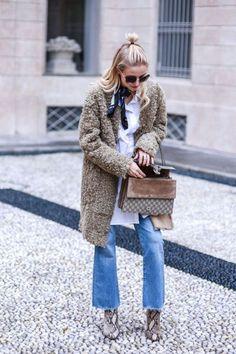 Look de inverno com calça jeans, bota estampada, fluffy coat, camisa branca e lenço no pescoço.