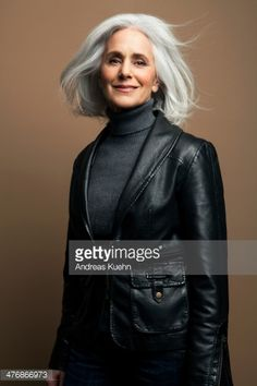 Mature woman with medium length, silvery, grey hair in front of a brown background wearing a black leather jacket with wind blowing in her hair.
