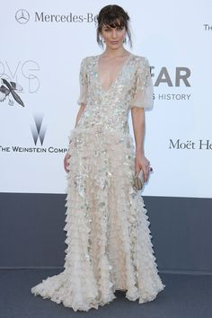 Cannes amfAR Gala May 23, 2013: Milla Jovovich wore a Valentino Couture spring/summer 2013 ruffled gown and carried a Jimmy Choo clutch.