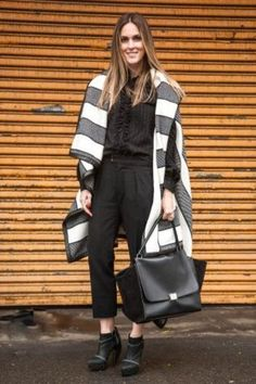 Shop this look on Lookastic: https://lookastic.com/women/looks/coat-button-down-blouse-dress-pants-ankle-boots-tote-bag/3650 — Black Leather Tote Bag — Black Leather Ankle Boots — Black Dress Pants — Black Chiffon Button Down Blouse — Charcoal Horizontal Striped Coat