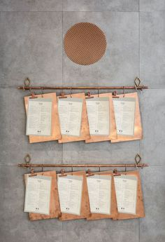 These menus on copper clipboards are hung on a copper pipe attached to the wall of a restaurant in Valencia.: