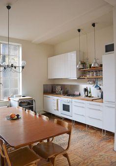 Matte white cabinets, butcher block counter, contrasting backsplash (mosaic?), pendant lights, some open shelving.
