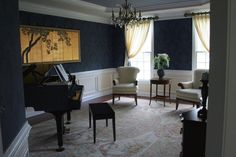 Dark walls make the room look important. Gold painting goes with desk.
