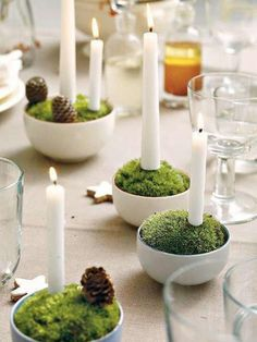 Moss & candle centerpieces: fill small bowls with floral foam, then cover with cushion moss. cut 5 cm plug wire with pliers, and push one end into the bottom of the candle, then push the candle into the moss. add pinecones or other decorations Candle Centerpieces, Christmas Centerpieces, Diy Candles, Christmas Decorations To Make, White Candles, Large Candles, Wedding Centerpieces, Wedding Decor, Candle Arrangements