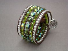 "Leather beaded bracelet made with emerald green round faceted, chartreuse green a/b rondelle, clear silver lined beads and silver tubes. Each bead is hand strung on 5 rows of 1.5 mm brown leather and finished with a round brown leather button closure. It measures 1.25"" high."