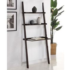 Make use of a small space with this brown leaning ladder shelf. The shelf fits snugly against the wall and can double as a laptop desk while the two smaller shelves provide storage. Shelves are composed of solid wood finished in a deep walnut color.
