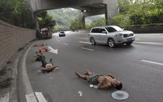 Labourers who work nearby nap on a road as cars drive past in Chongqing Municipality, July 23, 2013. (Photo by Reuters/Stringer)