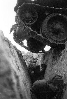 Soldados rusos atrincherados ante el paso de un tanque (Leningrado, 194X)    Esta fotografía, tomada en algún momento durante el sitio de Leningrado (San Petersburgo), muestra a un grupo de soldados soviéticos agazapados en una trinchera ante el paso de un tanque.