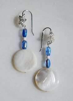 These kind of hip, kind of 60s-ish pierced earrings are fun! The round flat bead made from natural shell is topped by pretty blue iridescent