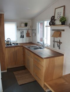 Liberation Tiny Homes kitchen. The kitchen relies on tried-and-true hanging storage for cutting boards, knives, and utensils with a petite table tucked against the wall, its two stools stored underneath.