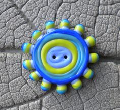 An eye catching button made using opaque lime green, turquoise, periwinkle and lapis. A fun button to add a one of a kind quality to any garment or bag!  Button measures approximately: 40mm at widest point  My buttons are made on a two hole button mandrel and go directly from the torch to my Chili Pepper kiln for proper annealing. Beads are cleaned of bead release and carefully packaged for shipping. Thanks for looking!! SRA #R114