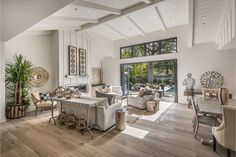 A vaulted, beamed ceiling towers above a great room with white oak flooring, a gas fireplace and accordion-style doors opening to the backyard. Photo: Paul Rollins