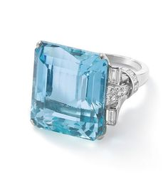 An aquamarine and diamond ring The rectangular cut-cornered aquamarine, approximately weighing between 30.00 – 35.00 carats, set to baguette- and single-cut diamond shoulders.
