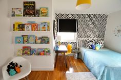 This room is bright, fun and stimulating. It features a small reading nook, graphic black-and-white wallpaper, and a small desk.