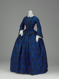 Woman's day dress, c. 1850, with skirt of blue silk ground with all-over black floral pattern and bodice of blue and black silk, jacquard-woven in a floral pattern, trimmed with ribbon and black silk fringe at front opening and hem.