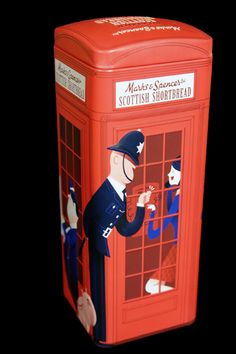 Marks and Spencer shortbread tin in the shape of and decorated as a red British phone box with figures including a British Bobby, city gent and punk