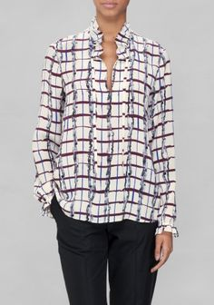 Made from soft mulberry silk, this blouse features a gathered collar and cuffs, creating feminine ruffles as a contrast to the edgy print.