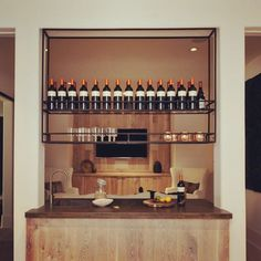 That time we couldn't figure out where to put the wet bar - so we custom built an insane floating iron rack (with rails - can't love the vino) and floated the bar - complete with dishwasher and fridge - between two columns in the media room. Now the bartender can serve from either side - Dana Lynch