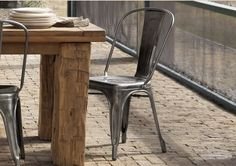 The contrast of sharp steel chairs against a warm, worn hardwood table makes me smile. =)