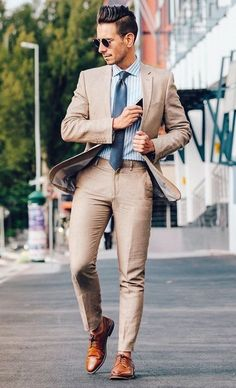 with a crisp dapper combo with a well tailor tan linen suit with a light blue white striped shirt blue tie brown brogues shoes sunglasses Costume En Lin, Mode Costume, Khaki Suits, Brown Suits, Beige Suits For Men, Guys In Suits, Tan Suit Men, Suit For Men, Style Costume Homme