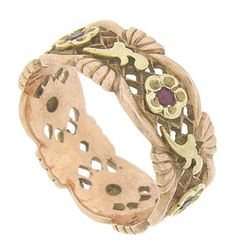 Simple latticework filigree framed in swags of rose gold adorn the surface of this 14K red gold wedding band. Abstract leaves and flowers crafted of yellow gold press into the rings surface. Round, faceted rubies are set into the face of each sparkling posy.  9.16 mm in width. Circa: 1940.