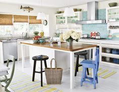 A striking sea glass-tiled backsplash and single blue chair bring hints of the ocean to this beachy kitchen.