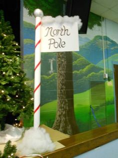 Homemade North Pole sign for my music program. Pole is the heavy cardboard from a roll of fabric painted with white acrylic then striped with painter's tape and painted with red acrylic. Finial is a plastic ball spray painted metallic silver. Sign is thick art board, handwritten. Display on a microphone stand and decorate with fluff--instant North Pole!