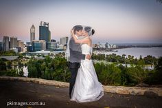 A wedding couple is kissing under a veil while standing in the Kings Park with the Perth city sunset panorama in the background.
