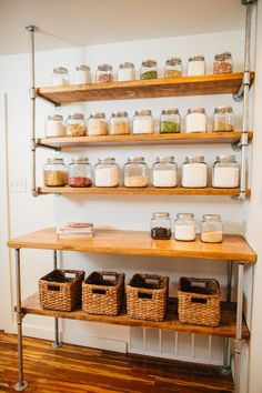 Canisters of spices sit on open shelving made from industrial piping and wood in natural finish.