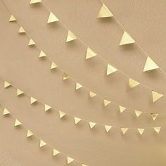 """DIY Geometric Triangle Garland Kit with gold foil 2"""" size triangles. Kit includes adhesive labels and string. Cut string to length and space and stick triangle banners as you prefer for your own DIY p"""