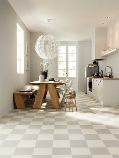 Pretty kitchen. Delicate feature light, timber table setting & pale grey/white checkered floor. So fresh!