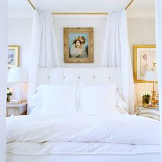 """""""No canopy bed? No problem. A system of rods suspended from the ceiling is a great impostor. Crisp panels are hung from the four corners and are mobile along the rods, just like curtains. The rods are painted to match the picture frames on the wall below. The white canopy enhances the airy feel of the white bedding."""""""