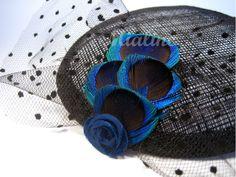 Fascinator aus den Pfauenaugen der Pfauenschwanzfeder. Verschönert mit gepunktetem Tüll und dunkelblauer Samtrose.