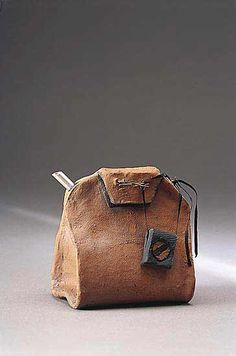 Raku-fired teapot with matte glaze and sterling spout, created to look like a tea bag.