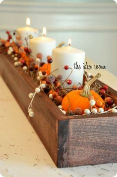 wooden box with pumpkins and candles and grapevine
