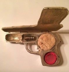 Ladies makeup compact fashioned in the shape of a pistol – complete with powder, cheek rouge and lipstick in the shape of a bullet, ca.1920