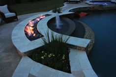 Complete with fountain bubblers and plantings on either side, this fire and water feature adds an exciting geometric element to the pool's design.  Paragon Pools, Texas http://www.luxurypools.com/articles/playing-with-fire-pool-designs-with-flare.aspx
