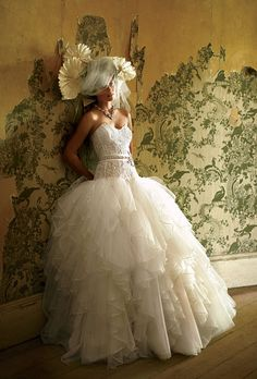Brides.com: . Check out the volume on this multilayered, ribbon-edged tulle skirt, topped with a belted, re-embroidered Alençon-lace bodice. Gown, $2,995, Eve of Milady. Ornaments (used as hair accessories), BHLDN. Necklace, Ben-Amun.