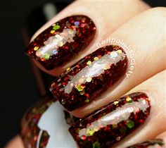 A Liquid Lacquer Nail Polish - Red Death has a blackened rust jelly base with red, silver, lime green and yellow glitter and dark red shimmer.