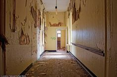 A crumbling and rotten hallway in the hospital with paint peeling from the walls (Lancaster Moor Hospital).
