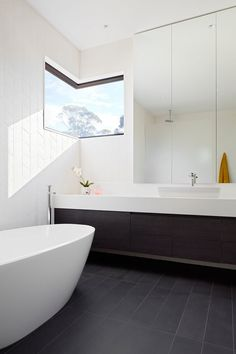 In this bathroom, floor-to-ceiling tiles line the walls, and a corner window allows for lots of light to enter the space.