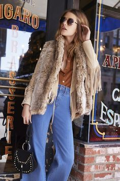 High waist jeans and a fur vest over a classic 70s jacket - cool style.