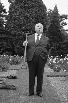 Alfred Hitchcock stands with a pitchfork on the lawns of Pinewood Studios