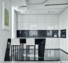 Стол на кухне сделан по чертежам авторов проекта. Он идеально сочетается с геометрией потолочных светильников и мраморных плит на полу. Барные стулья Andoo, Walter Knoll. Кухонный гарнитур Viva, Maistri Innovation.